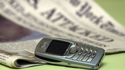 A mobile phone next to a newspaper