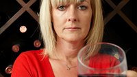 Jane Moore holding a glass of wine