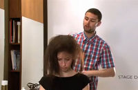 A hair stylist backcombing a woman's hair