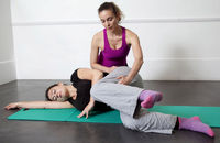A pilates instructor teaches exercises to strengthen and tone the hips