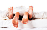 Couple under the sheets with their feet sticking out