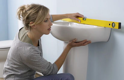Woman fitting a bathroom sink