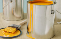 tin of yellow paint and brush. how to paint