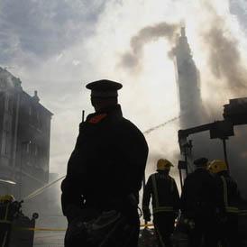 A policeman overlooks destroyed buildings in Tottenham. (Reuters)