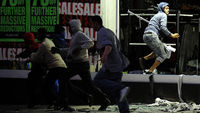 Looters run from a clothing store in Peckham. Missiles were hurled at police in London as violence broke out in the British capital for a third night in a row. (Reuters)