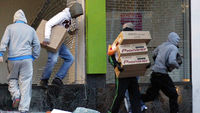 Birmingham riots: youths take hi-fi equipment during looting. (Reuters)