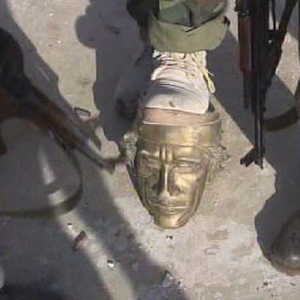 Gaddafi statue attacked by rebels.