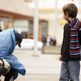 A boy looks back at a homeless man (Getty)