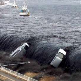 The tsunami breeching an embankment and flowing into the city of Miyako in Iwate prefecture (Getty)