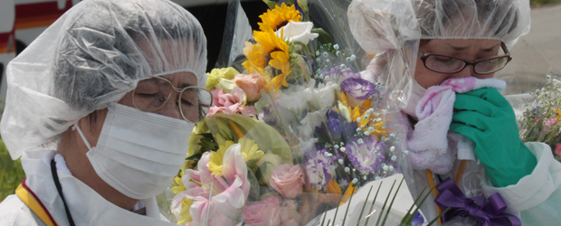 Former residents of the town of Okuma near the stricken Fukushima Daiichi nuclear power plant wipe away tears during a memorial service for the victims of the quake and tsunami (Getty)
