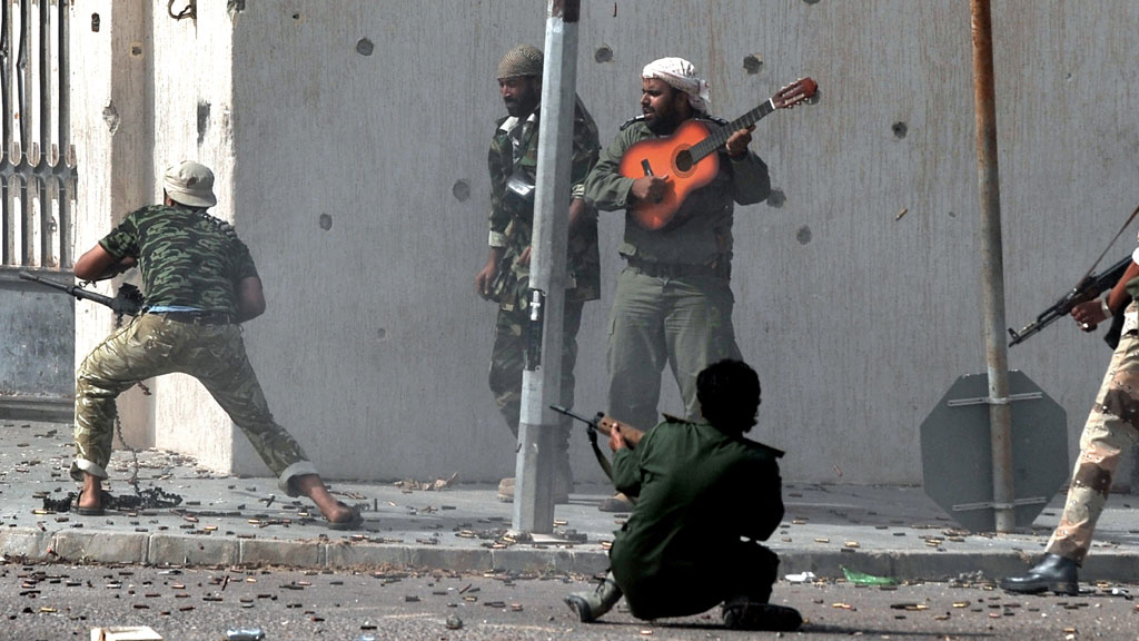Libya's new regime forces fire their weapons at fighters loyal to Colonel Gaddafi as a comrade plays a guitar during a battle in Sirte on October 10, 2011, (Photo credit: ARIS MESSINIS/AFP/Getty Image