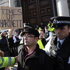 A protester holding a placard referring to Her Majesty's Revenue and Customs (HMRC) boss Dave Hartnett, takes part in a demonstration against corporate tax avoidance in London (Getty)
