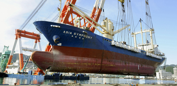 The 4,724-ton freighter Asia Symphony is lifted from land before being moved to the sea at Kamaishi port in Kamaishi (Reuters)