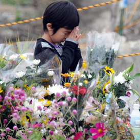 A boy prays for victims of the earthquake and tsunami at an altar set up in front of the Okawa elementary school at the city of Ishinomaki, Miyagi prefecture (Getty)