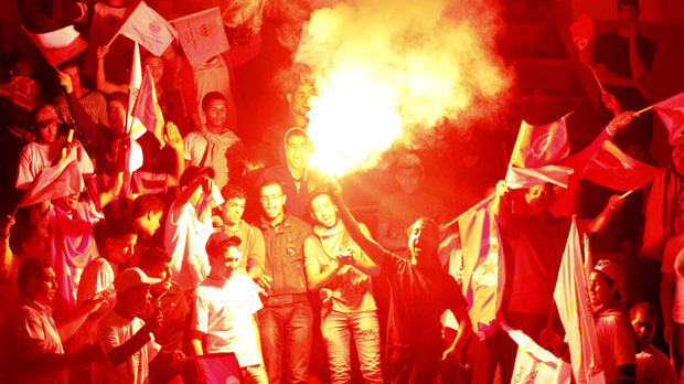 Supporters of Tunisia's Progressive Democratic Party (PDP) light flares during a closing campaign rally in Tunis (Reuters)