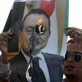 An anti-Mubarak demonstrator burns a picture of former Egyptian president Hosni Murbarak in front of the police academy where his trial is taking place in Cairo