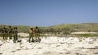 Kenyan police officers patrol the beach at Kiwayu Safari Village resort, where David Tebbutt was killed and his wife Judith abducted (Reuters)