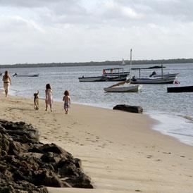 Tourists walk along the beach at Kiwayu Safari Village, where British holidaymaker David Tebbutt was killed and his wife Judith kidnapped (Reuters)