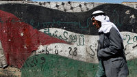 A Palestinian man walks past a flag mural (Reuters)