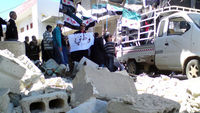 Demonstrators with the Syrian opposition flags protest against Syria's President Bashar Al-Assad after Friday prayers in Al Qasseer city, near Homs (Reuters)