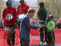 Britain's Prince Harry presents the women's award to Kenya's Mary Keitany and her son. She retained her women's title in two hours 18 minutes and 37 seconds.