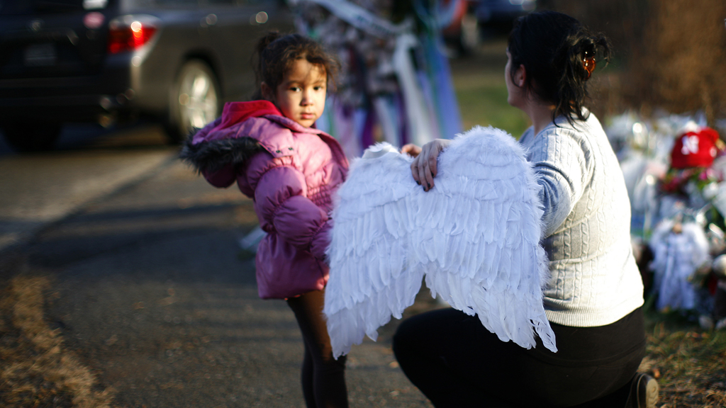A girl and a woman place angel wings at the Sandy Hook Elementary School sign in Newtown (R)