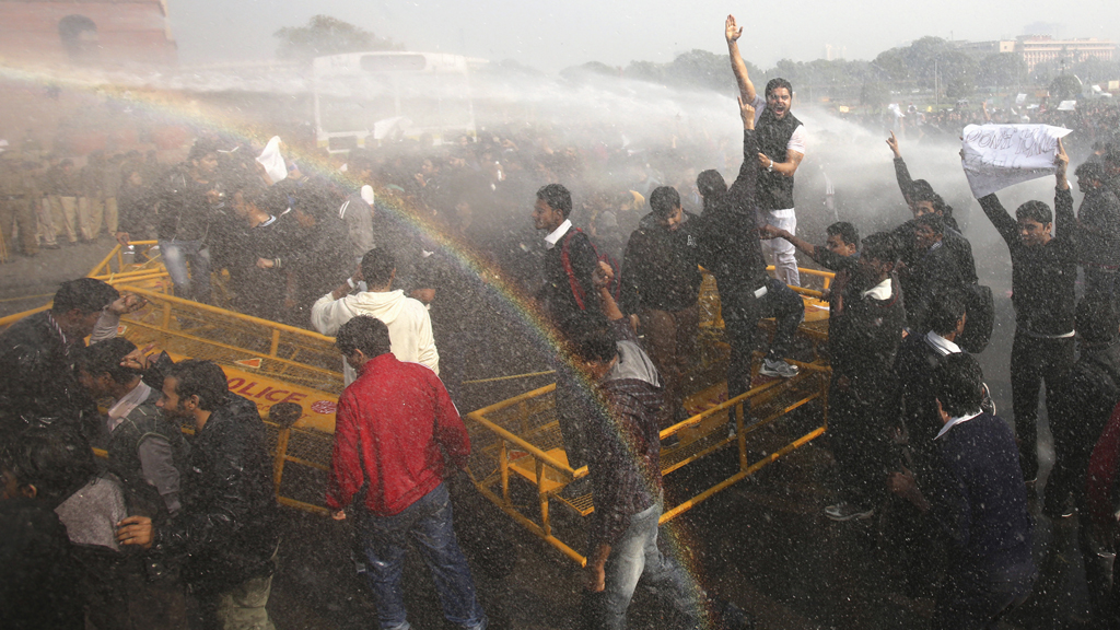Protestors break through a barricade as police fire water cannons (Reuters)