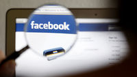 A magnifying glass held over a Facebook page (Reuters)