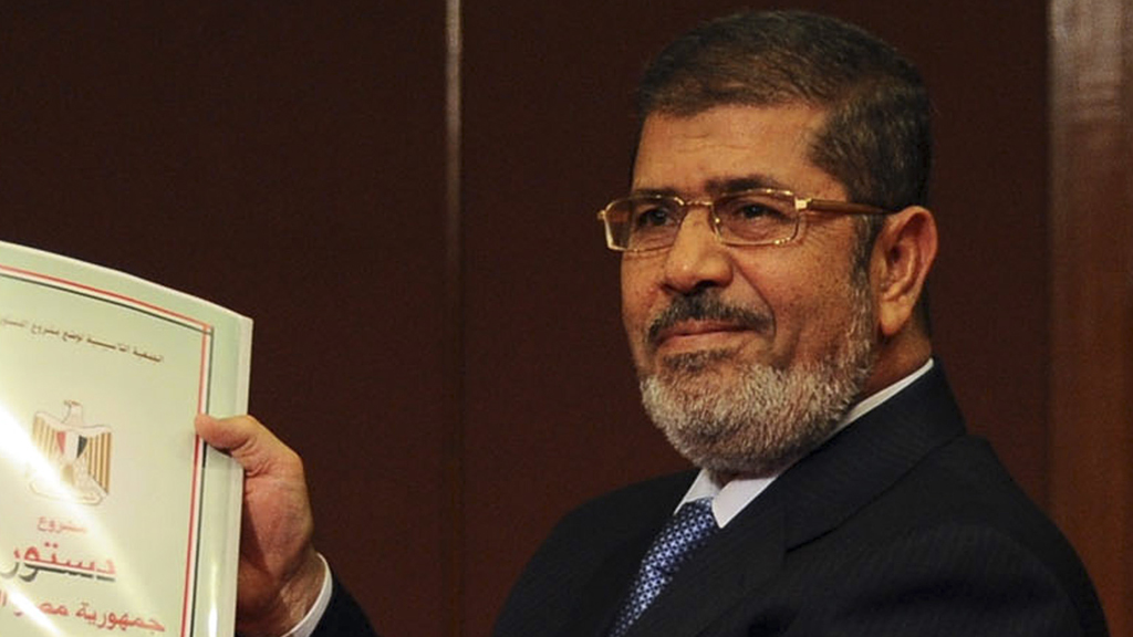 Mohamed Mursi holding the draft constitution (Reuters)