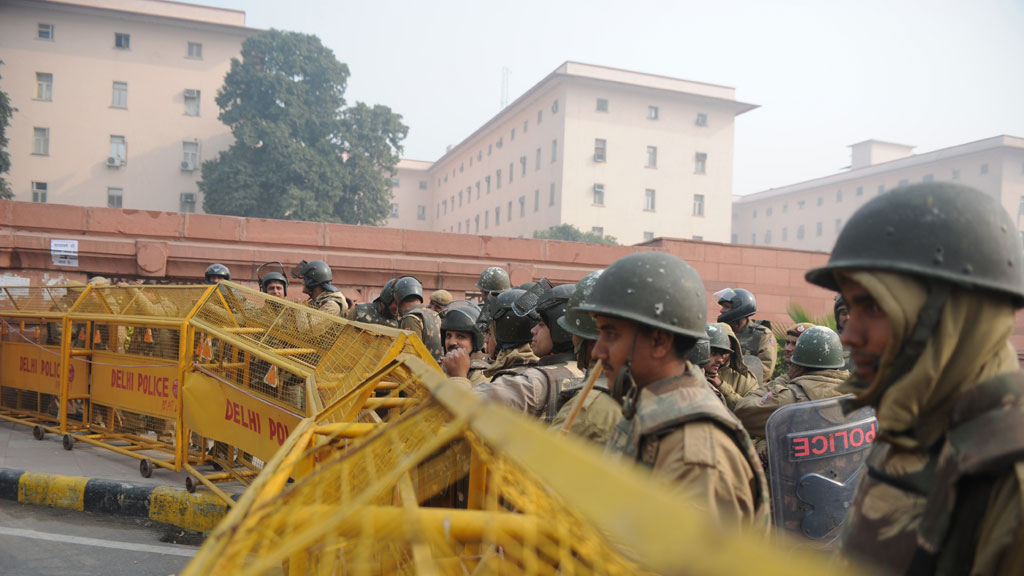 Indian riot police look on as they keep watch along a sealed-off road in Delhi (pic: Getty)