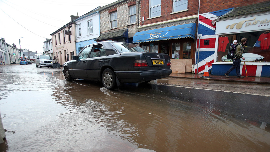 A car drives through flood waters in the centre of the Devon town of Braunton. (Getty)