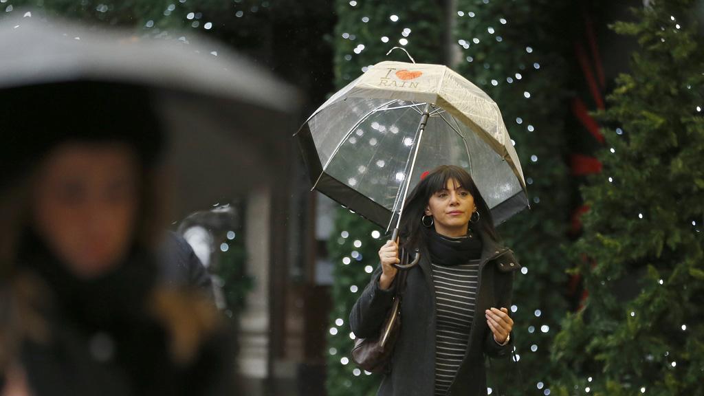 A woman shopping under an umbrella. (Reuters)