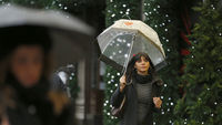 A woman shopping under an umbrella. (Reuters)
