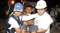 A man injured in a fire is carried by medical personnel in Comayagua (Reuters)