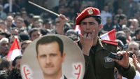 An image of Syrian President Bashar al-Assad is seen as Syrians take to the streets after voting on a new constitution that could end five decades of single-party domination, in the capital Damascus