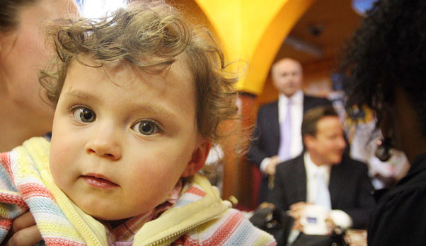 A child in a London nursery with Iain Duncan Smith and David Cameron in background (Getty)