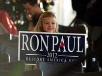 A girl holds up a yard sign at Ron Paul's campaign event in Kirkwood, Iowa, on the last day of campaigns. (Tawanda Kanhema)