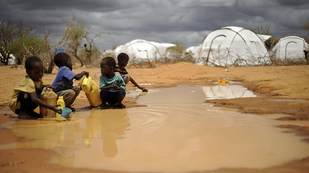 Children playing in a puddle in Dadaab refugee camp Kenya (Getty)