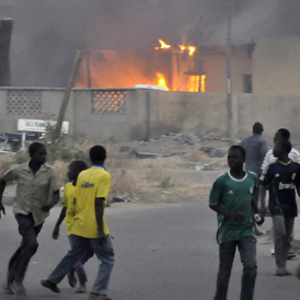 Smoke rises from the police headquarters as people run for safety in Nigeria's northern city of Kano (Reuters)