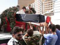 Loading up coffins of dead government soldiers as military hospital comes under fire - funerals were cancelled.