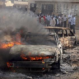 A car burns at the scene of a bomb explosion at St. Theresa Catholic Church at Madalla (Reuters)