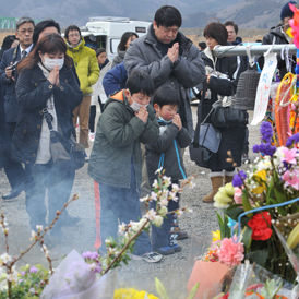 A family pray for 74 elementary school children and 10 teachers who lost their lives in the March 11 earthquake and tsunami, at a memorial in front of the Okawa elementary school (Getty)