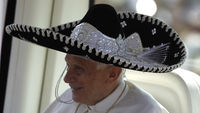 Pope Benedict XVI wears a traditional Mexican hat while being driven through a crowd before officiating mass in Silao (Reuters)