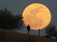 A runner makes his way along a trail in front of the 'super moon' at Papago Park, Phoenix, Arizona, 5 May 2012.