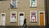 A man walks past boarded up houses in Burnely (Reuters)