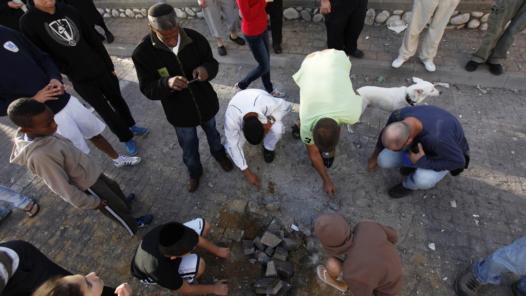Israelis survey damage from a rocket that hit the southern city of Ashod (Reuters)