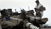Israeli soldier prays atop a tank near border with Gaza (Reuters)