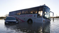 A stranded car and bus are surrounded by flood waters from the River Soar near Mountsorrel (Reuters)