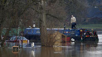 A man stands stranded on his boat surrounded by flood waters from the River Soar in Barrow Upon Soar (Reuters)