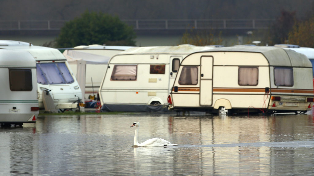 A swan swims through flood waters from the River Soar at a caravan park in Barrow Upon Soar (Reuters)